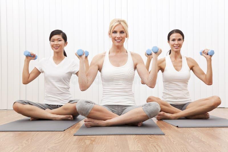 As mulheres inter-raciais do grupo da ioga tornam mais pesado o treinamento fotografia de stock