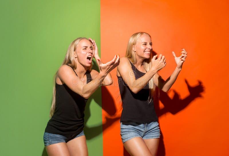 As mulheres irritadas emocionais novas que gritam no fundo do estúdio foto de stock
