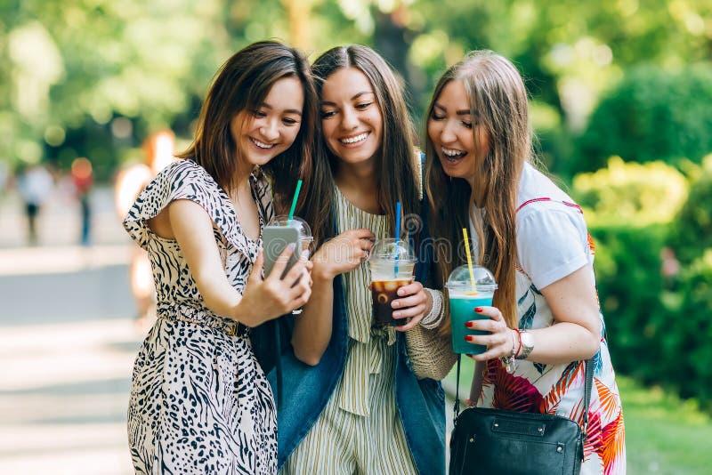 As mulheres multirraciais do retrato do estilo de vida do verão apreciam o dia agradável, guardando vidros dos milks shake Amigos fotos de stock