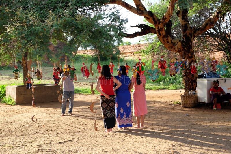 As mulheres não identificadas de Myanmar estão sendo tomadas a foto com fantoches tradicionais ao redor foto de stock