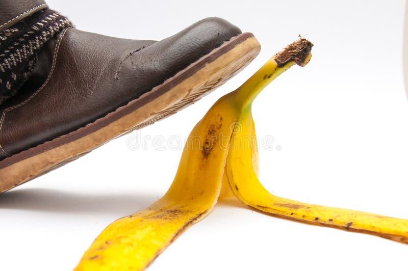 As mulheres na sapata de couro marrom que pisam na banana descascam imagem de stock royalty free