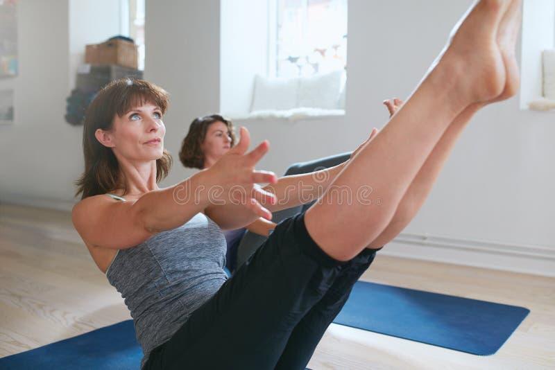 As mulheres no barco completo levantam durante a sessão da ioga foto de stock royalty free