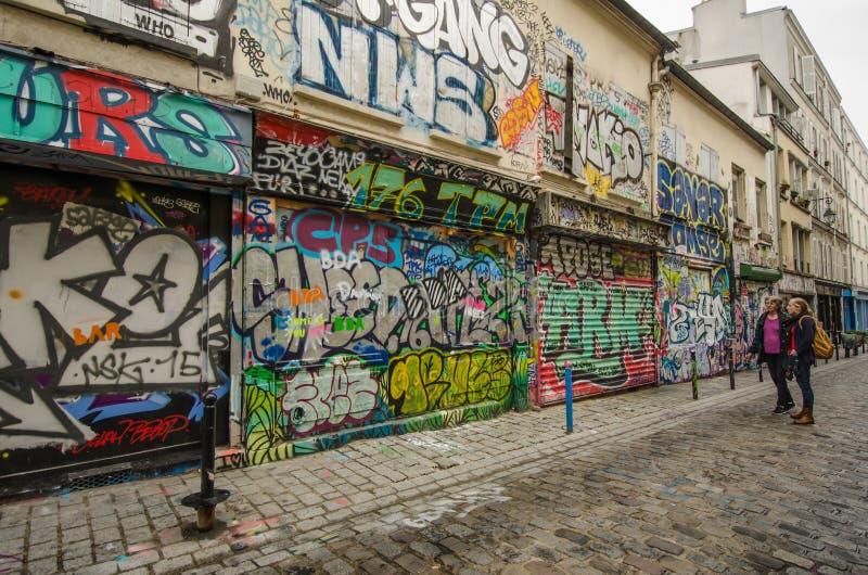 As mulheres olham os grafittis coloridos em Rue Denoyez em Paris foto de stock