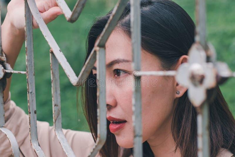 As mulheres olham para fora e estando guardando a malha de aço imagens de stock royalty free