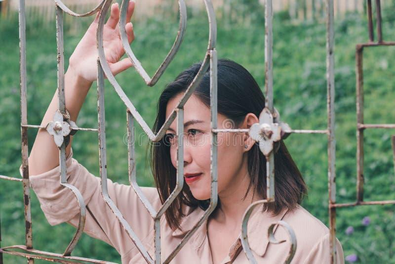 As mulheres olham para fora e estando guardando a malha de aço fotografia de stock