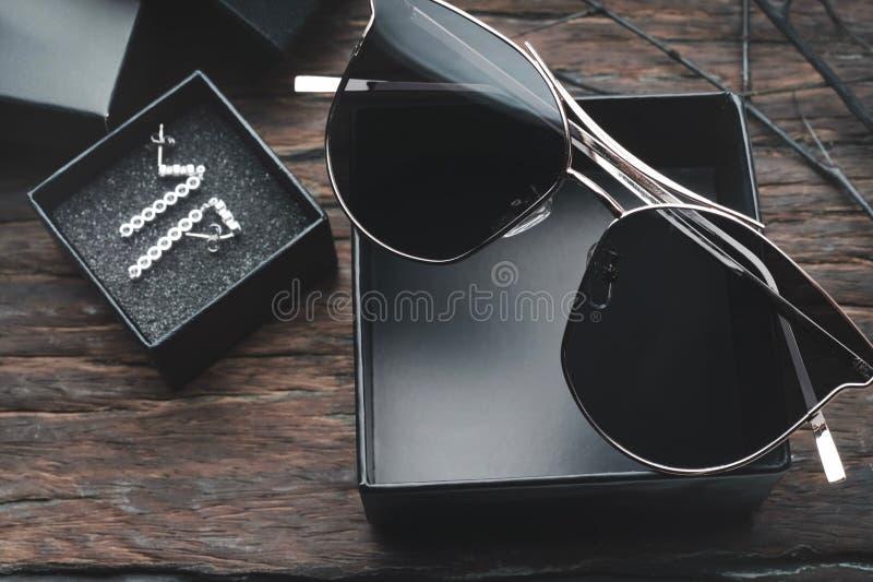 As mulheres ou os óculos de sol na moda do homem formam óculos de sol e teclado no fundo de madeira da tabela fotografia de stock