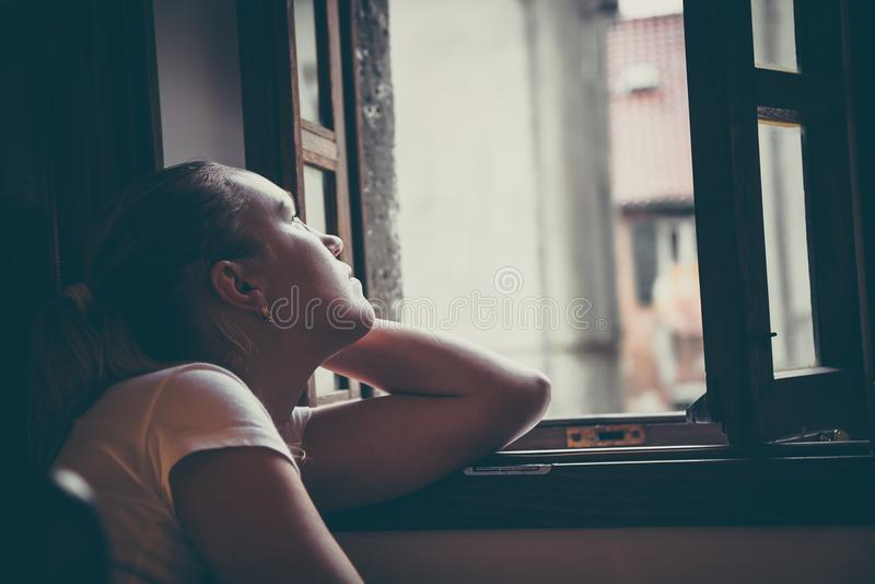 As mulheres pensativas sós com expressão pensativa perderam nos pensamentos que pensam e que olham na janela aberta no estilo do  imagens de stock