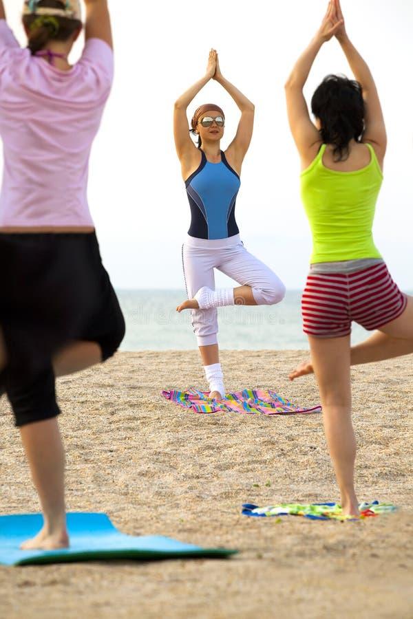 As mulheres que fazem a aptidão exercitam em uma praia fotografia de stock