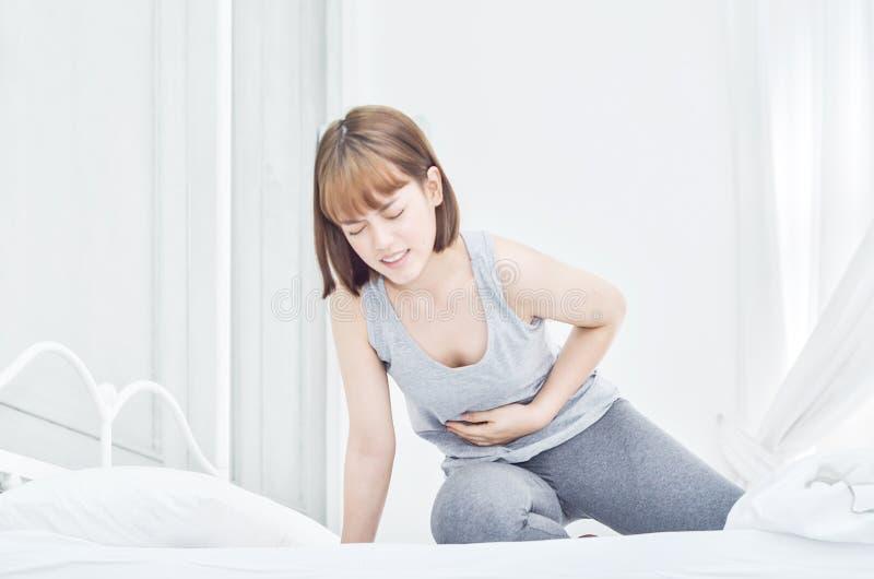 As mulheres têm a dor abdominal no colchão fotografia de stock