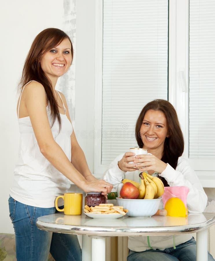 As mulheres têm o chá na cozinha foto de stock