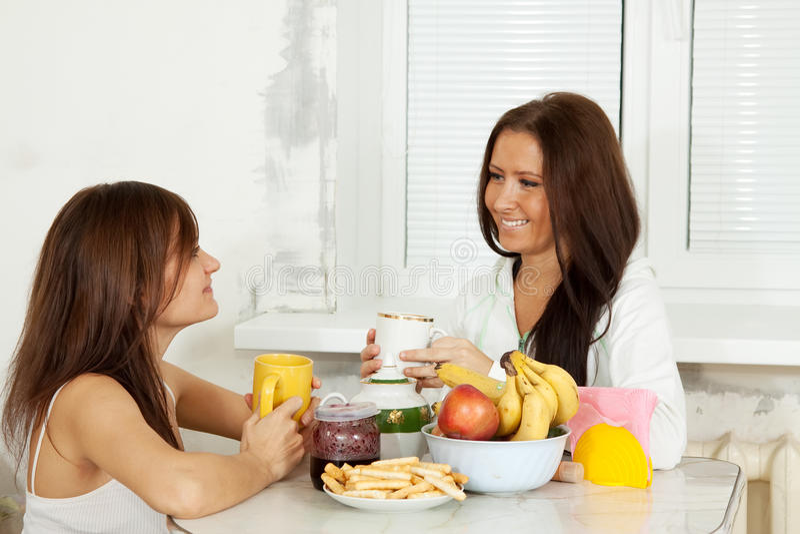 As mulheres têm o chá na cozinha foto de stock royalty free