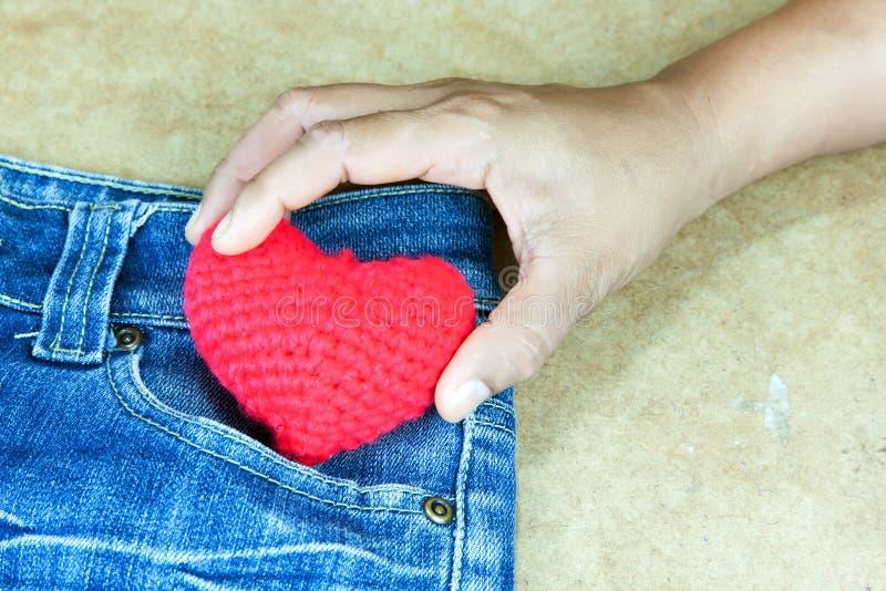 As mulheres tomaram ao coração fazer crochê a cor vermelha imagem de stock