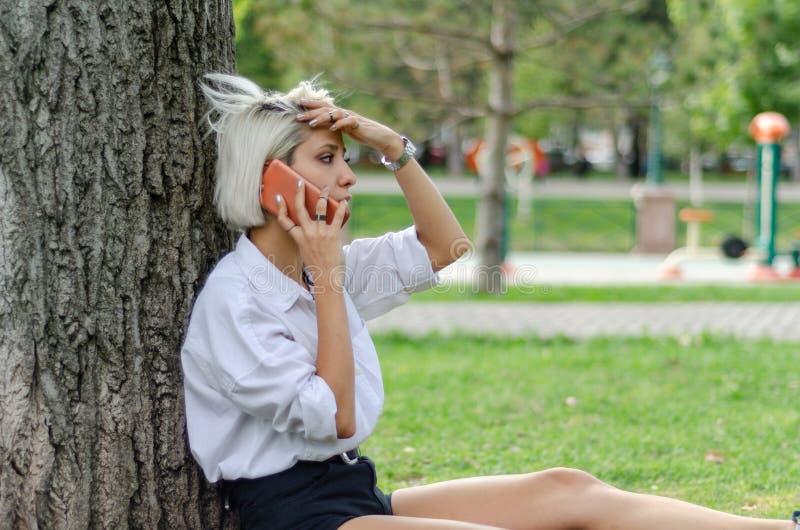 as negociações da jovem mulher a seu telefone celular imagem de stock