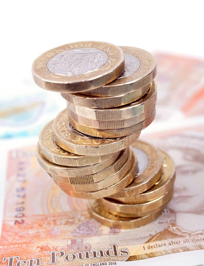 As notas e as moedas brit?nicas do dinheiro empilham foto de stock