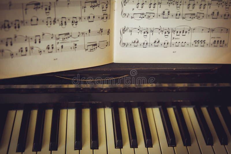As notas encontram-se em um piano preto Chaves brancas foto de stock