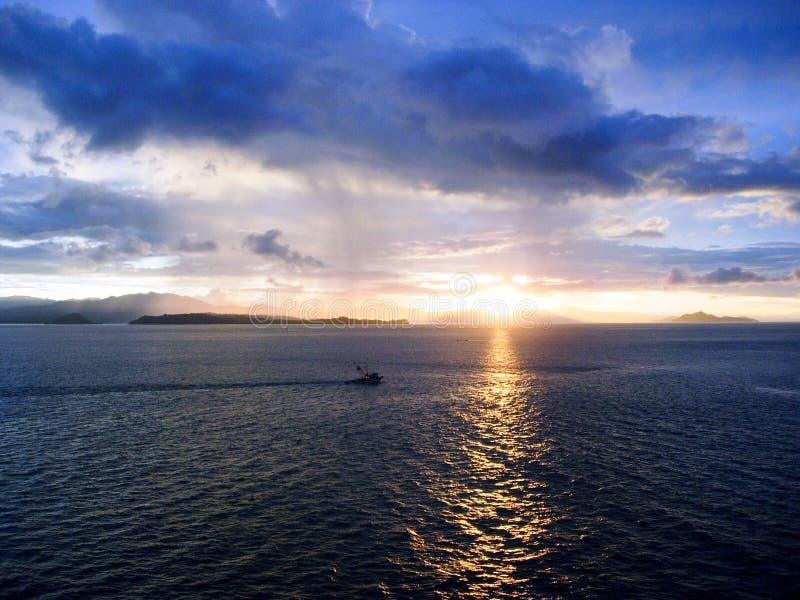 As nuvens azuis refletem o nascer do sol no mar dentro do canal do Panamá imagem de stock