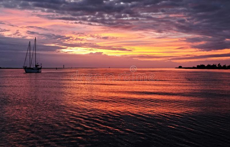 As nuvens carmesins vívidas e o seascape do nascer do sol do céu com água refletem fotografia de stock royalty free
