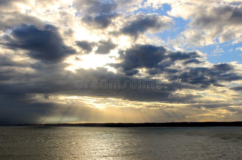 As nuvens chovendo e o oceano no por do sol imagens de stock