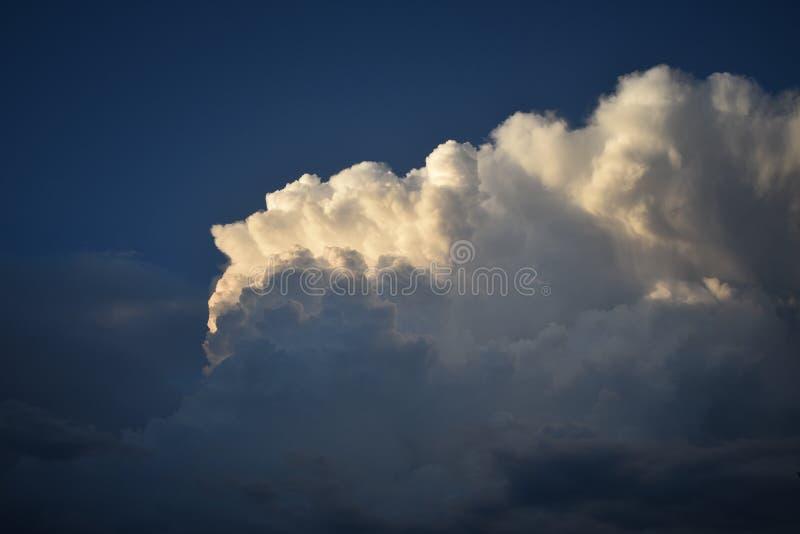 As nuvens coloridas, densas, maciças no céu da noite imagens de stock royalty free
