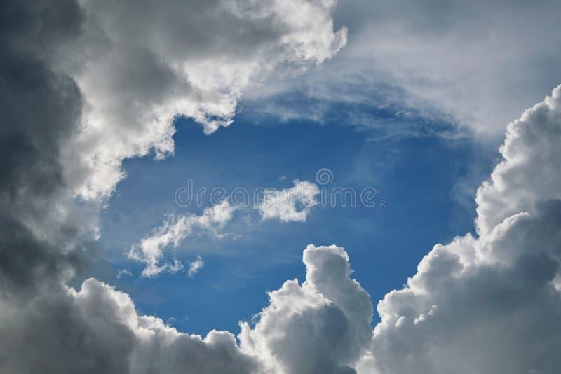 As nuvens de cúmulo tormentosos são cercadas por um céu azul claro foto de stock