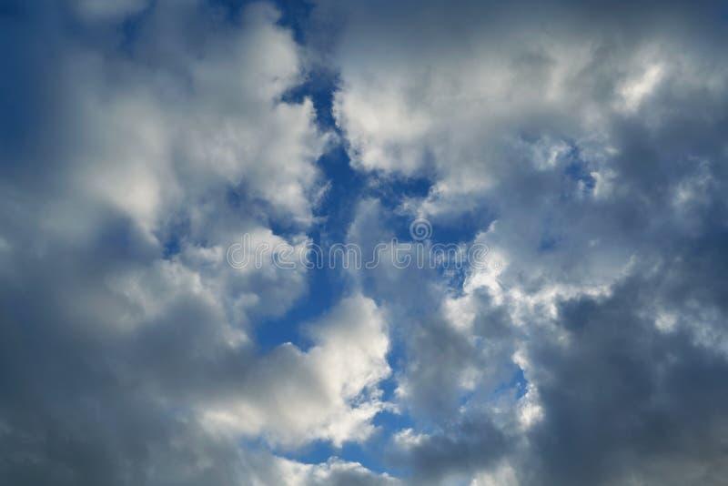 As nuvens de chuva rastejam em ambos os lados e cobrem o céu azul claro imagem de stock