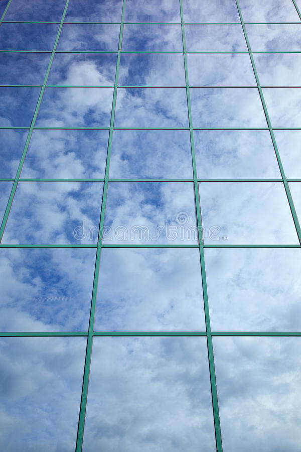 As nuvens e o céu azul refletiram na fachada de vidro fotos de stock royalty free