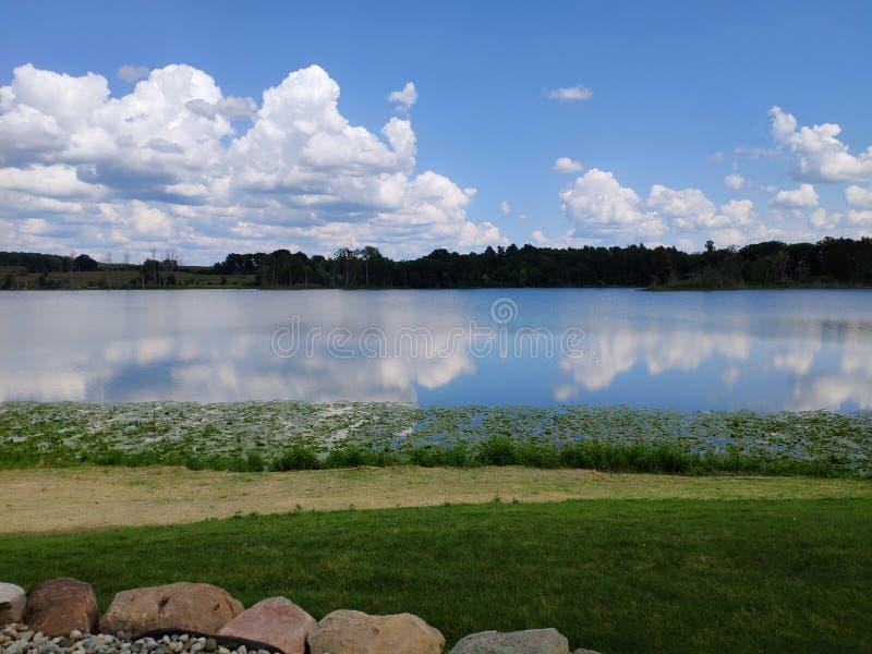 As nuvens e o céu refletem no lago fotos de stock