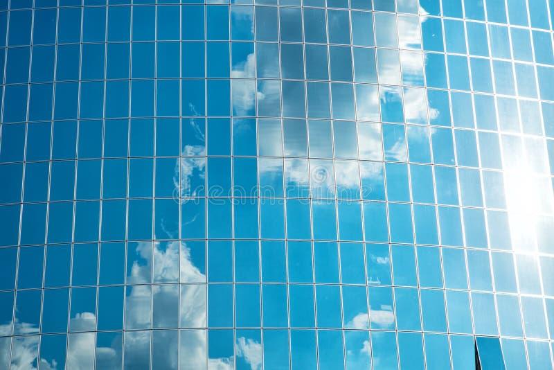 As nuvens refletiram na parede de vidro da fachada da construção Reflexão nebulosa do céu azul nas janelas Arquitetura de vidro m fotos de stock royalty free