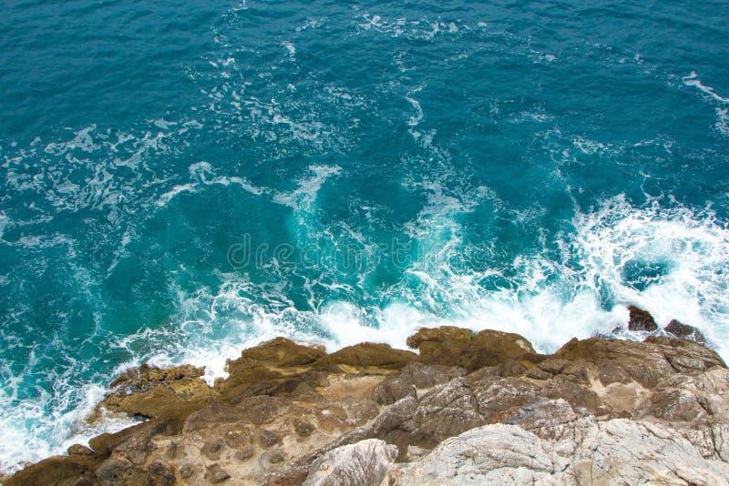 As ondas azuis do mar dos azuis celestes deixam de funcionar nas rochas A espuma branca bonita espalha em todos os sentidos Fundo fotografia de stock