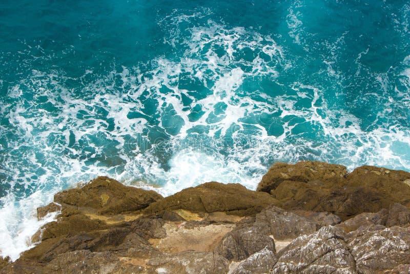 As ondas azuis do mar dos azuis celestes deixam de funcionar nas rochas A espuma branca bonita espalha em todos os sentidos Fundo fotos de stock