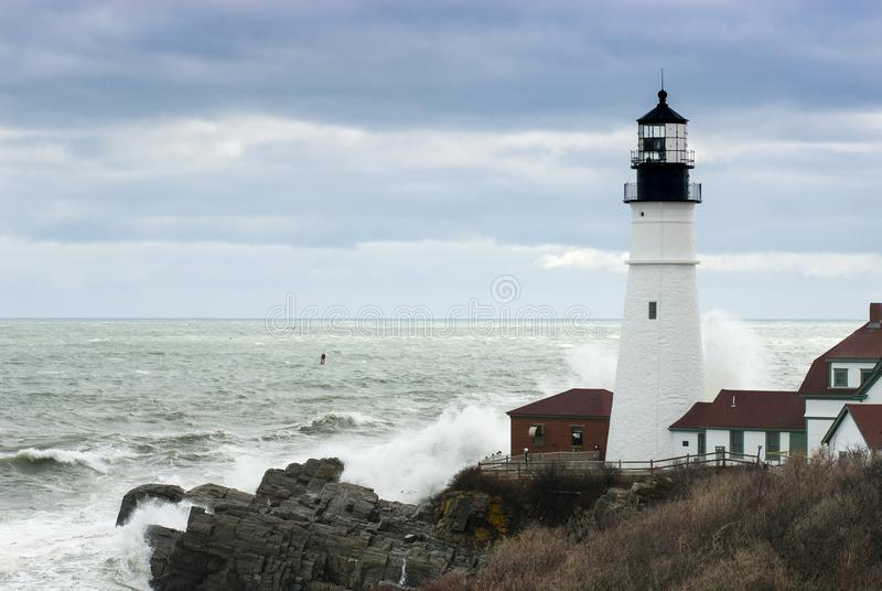 As ondas deixam de funcionar contra Maine Lighthouse enquanto Sun quebra completamente fotografia de stock royalty free