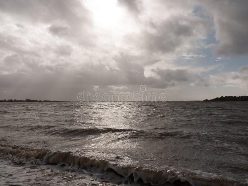 As ondas deixando de funcionar do mar com as nuvens dramáticas do céu suportam fotografia de stock