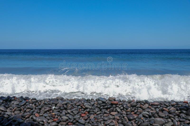 As ondas do mar que batem a costa rochoso acenam a volta na espuma do mar Água do mar espumoso e bolhas A água da matança de Açor foto de stock