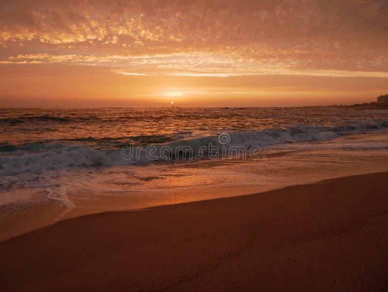 As ondas grandes quebram na praia no por do sol em Portugal com céu bonito fotografia de stock