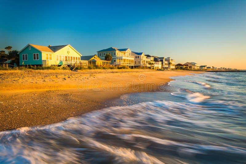 As ondas no Oceano Atlântico e na manhã iluminam-se na casa beira-mar imagens de stock