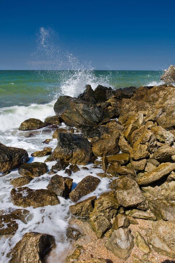 As ondas que espirram na praia com as rochas fotografia de stock