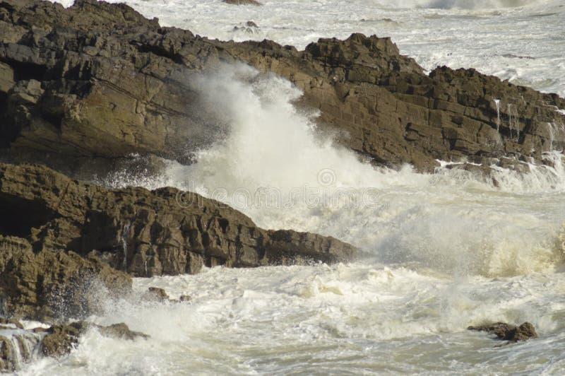 As ondas que quebram sobre rochas próximo murmuram, Gales, Reino Unido foto de stock