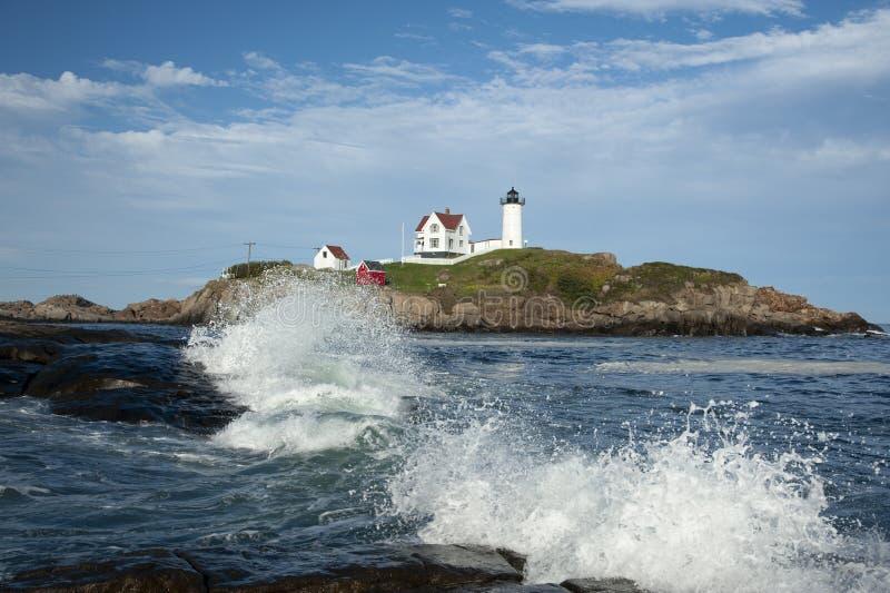 As ondas quebram em torno do farol do Nubble em um dia de verão em Maine imagem de stock royalty free