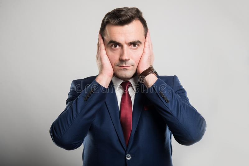 As orelhas atrativas da coberta do homem de negócio gostam do gesto surdo fotografia de stock