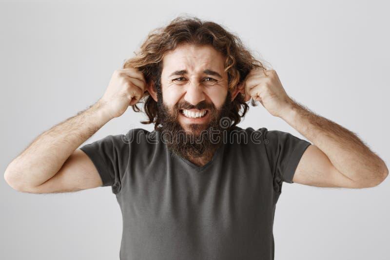 As orelhas são cansados das mentiras da audição Tiro do estúdio do indivíduo maduro incomodado e comprimido com puxar da barba e  fotografia de stock