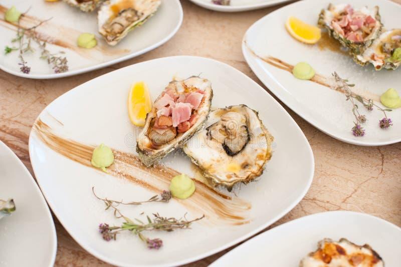 As ostras cozinhadas em uma grade encontram-se em uma placa branca imagens de stock royalty free