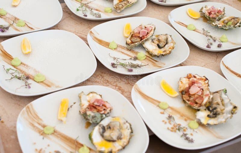 As ostras cozinhadas em uma grade encontram-se em uma placa branca fotos de stock royalty free