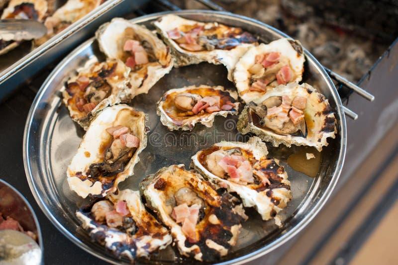 As ostras cozinhadas na grade encontram-se em uma bandeja fotos de stock