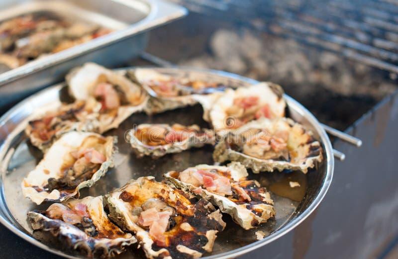 As ostras cozinhadas na grade encontram-se em uma bandeja fotografia de stock