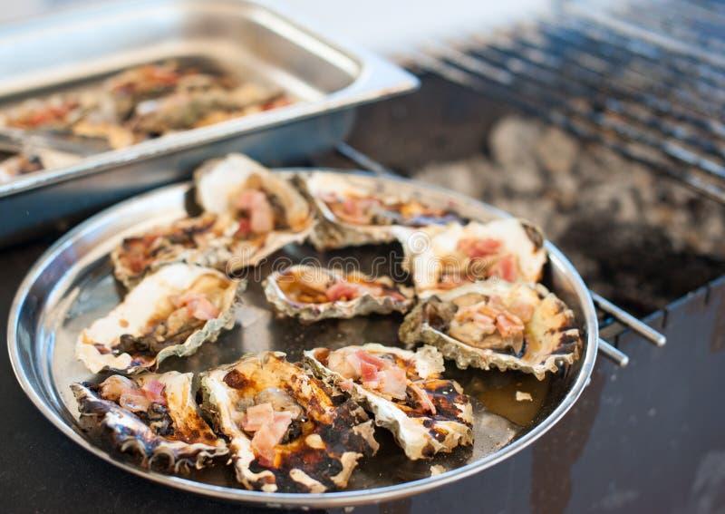 As ostras cozinhadas na grade encontram-se em uma bandeja imagens de stock