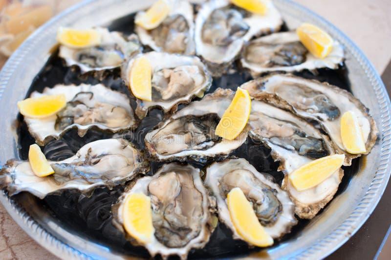 As ostras frescas encontram-se em uma bandeja de gelo e de limão imagens de stock royalty free