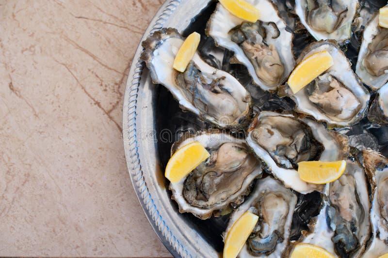 As ostras frescas encontram-se em uma bandeja de gelo e de limão imagens de stock