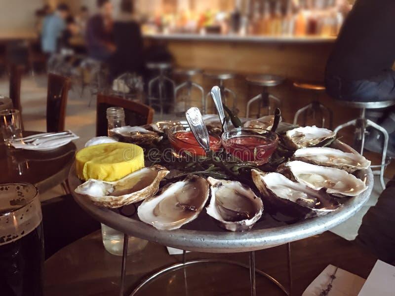 As ostras no gelo chapeiam servido com o limão e o molho na barra de ostra fotografia de stock