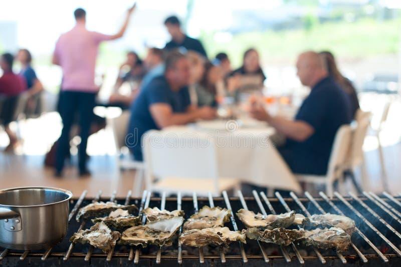 As ostras são cozinhadas na grade entre os visitantes do café imagens de stock royalty free