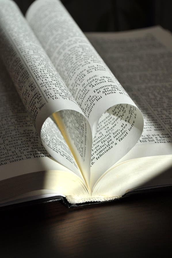As páginas do close up de um livro aberto, com coração deram forma a páginas foto de stock royalty free